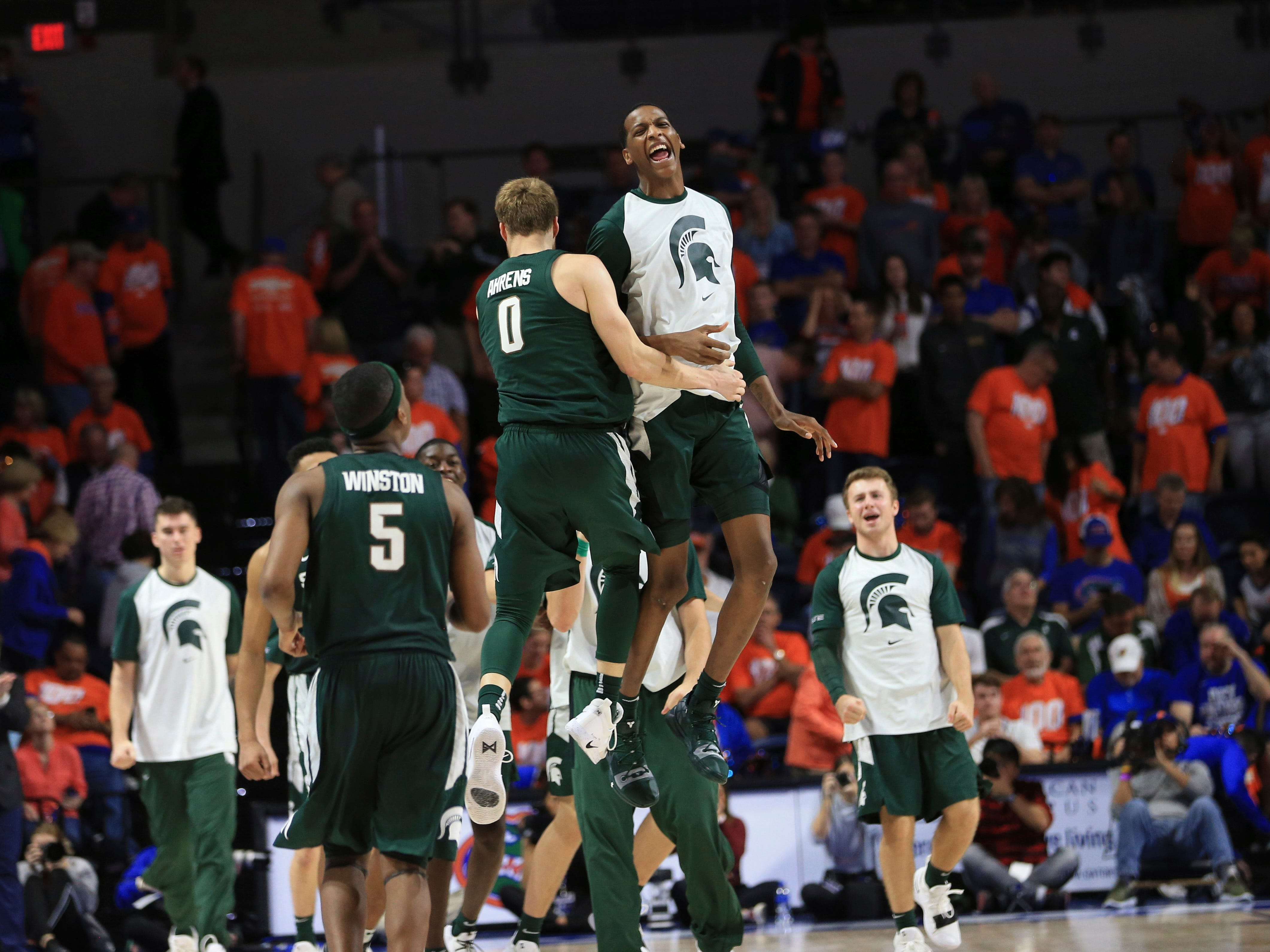 Michigan State forwards Kyle Ahrens (0) and Marcus Bingham Jr. (30) celebrate after an NCAA college basketball game against Florida, Saturday, Dec. 8, 2018, in Gainesville, Fla. Michigan State defeated Florida 63-59.
