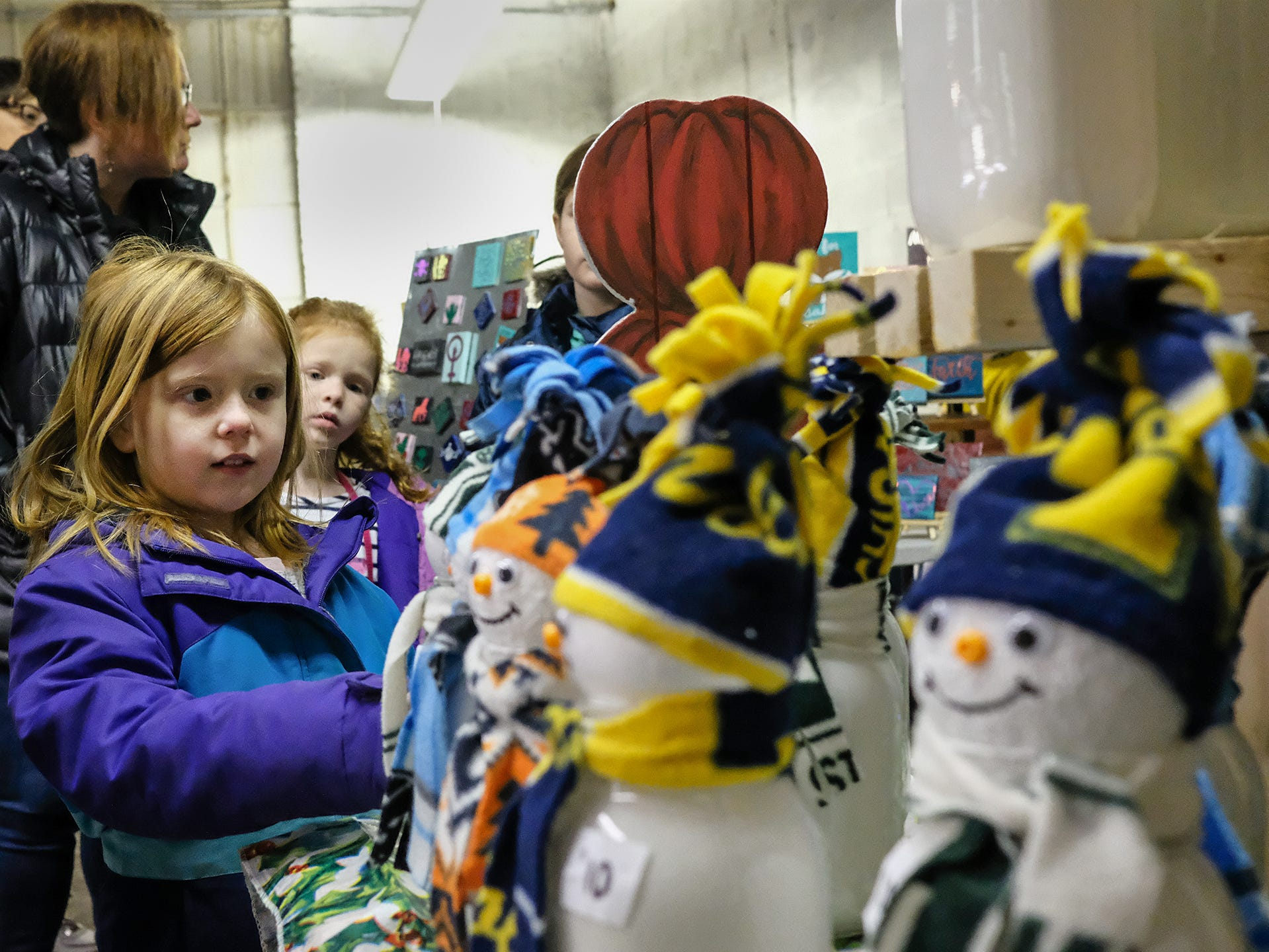 Kirsten Gibson, 7, from Lansing, checks out the mason jar snowmen made by pop-up vendor, Art by Autumn J. at the Reo Twon Marketplace Saturday, Dec. 8, 2018.