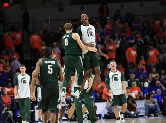 Michigan State's Kyle Ahrens (0) and Marcus Bingham Jr. (30) celebrate after the Spartans' 63-59 win over Florida on Saturday.