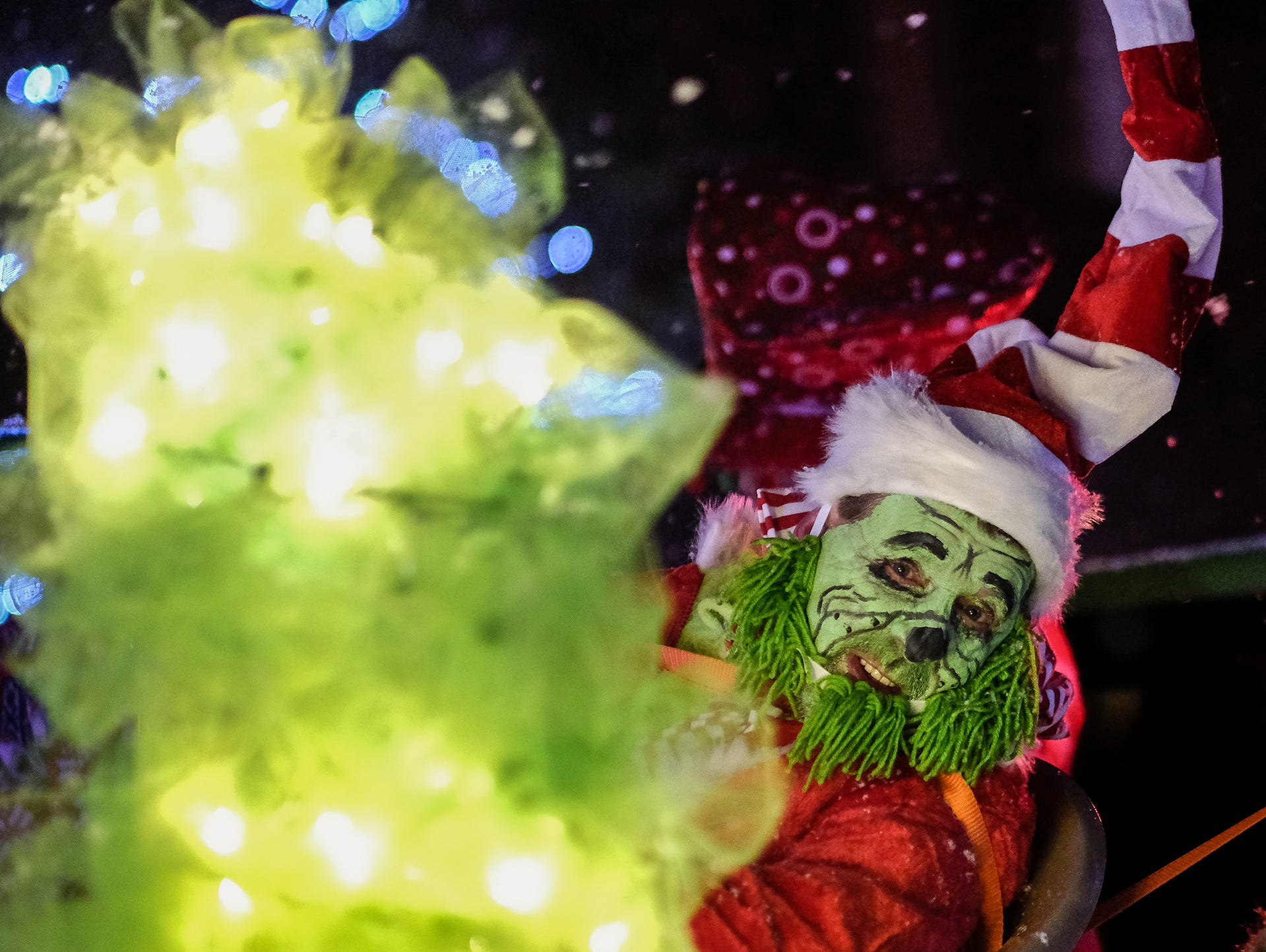 A grinch peeks around a lighted tree at the Annual Festival of Lights and Santa Parade in downtown St. Johns Friday, Dec, 7, 2018.