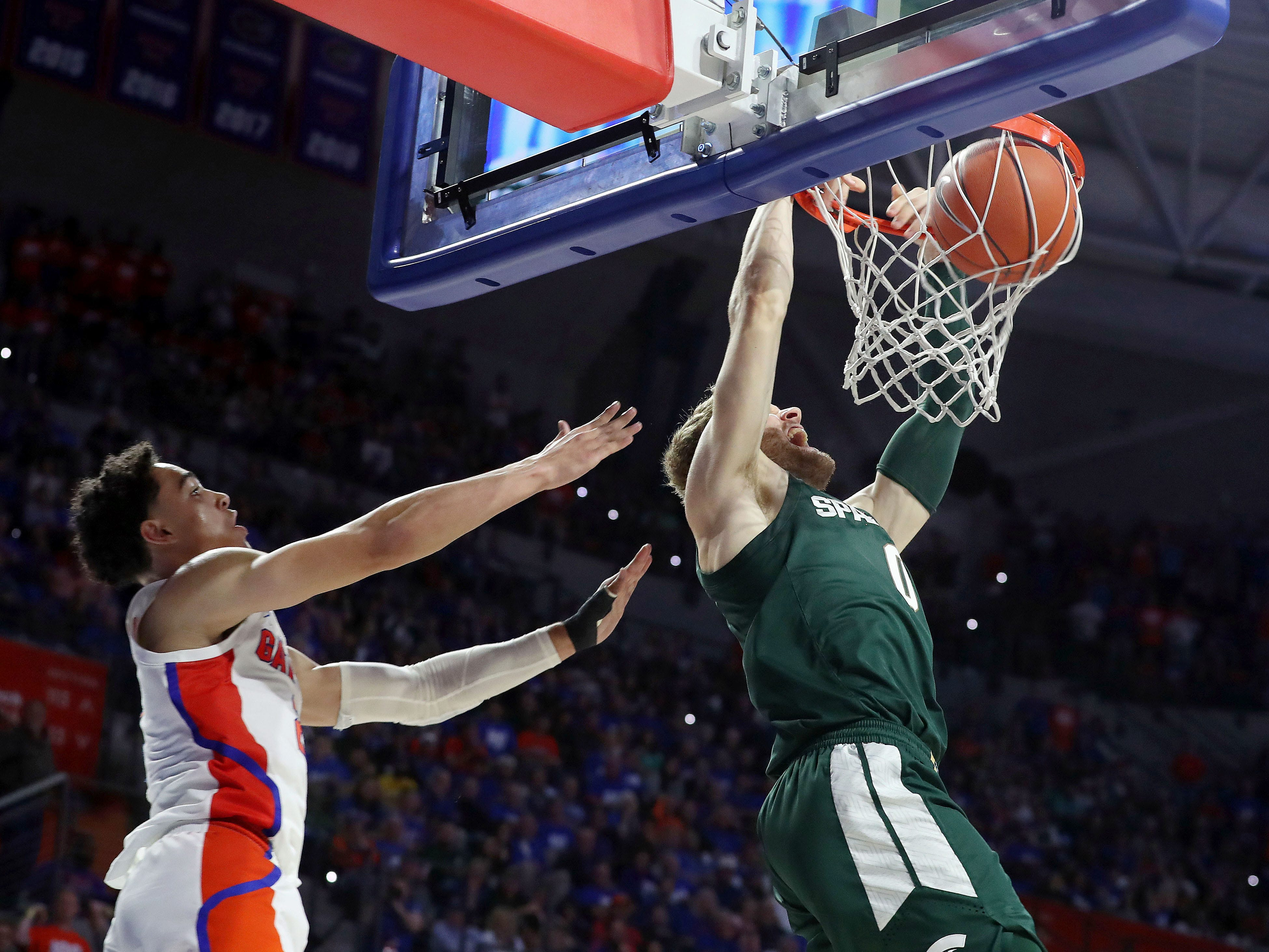 Michigan State Spartans forward Kyle Ahrens (0) dunks over Florida Gators guard Andrew Nembhard (2) during the second half at Exactech Arena.