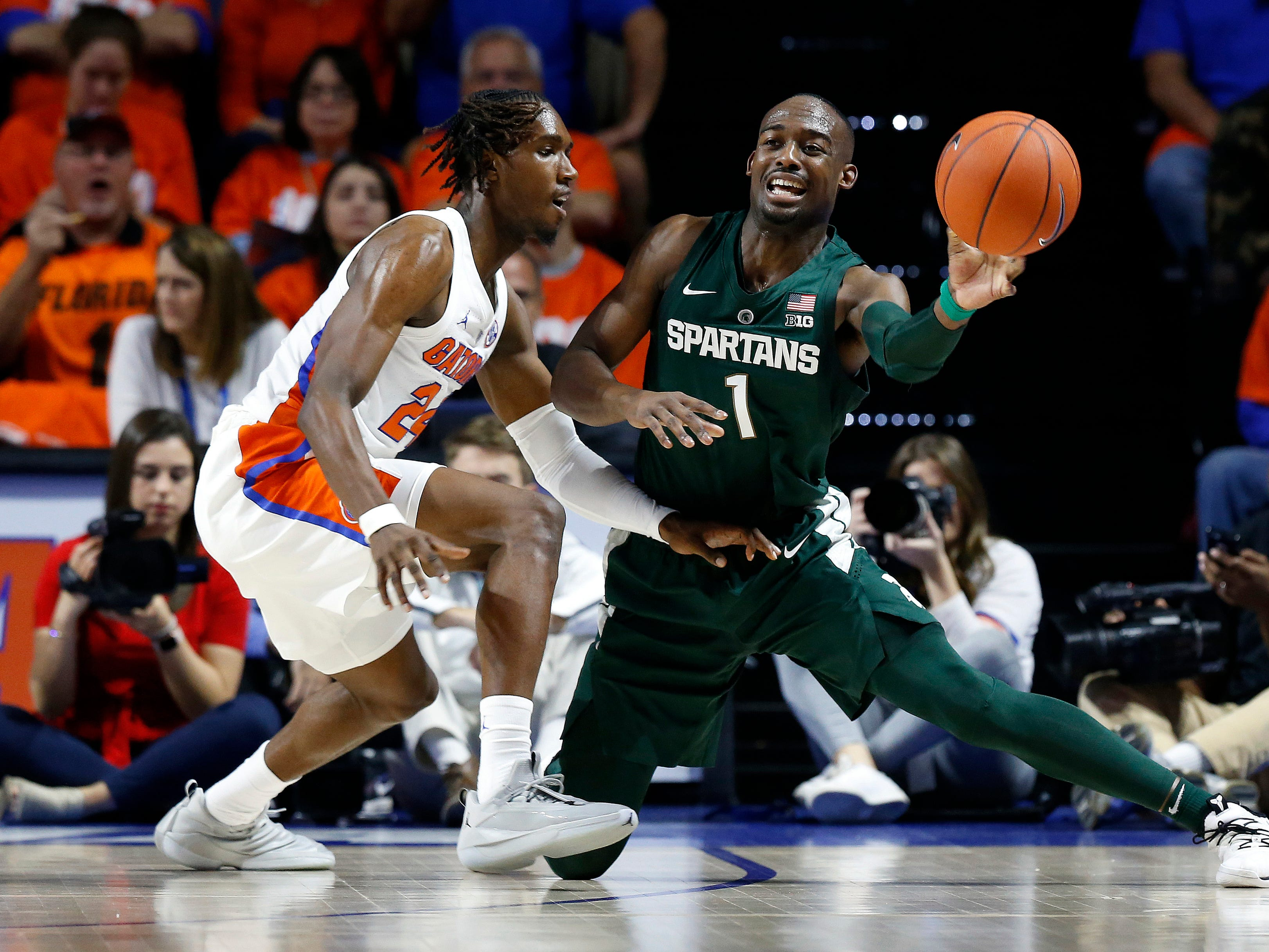 Michigan State Spartans guard Joshua Langford (1) passes as Florida Gators guard Deaundrae Ballard (24) defends during the first half at Exactech Arena.