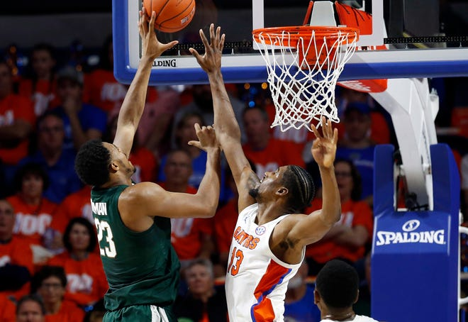 Michigan State Spartans forward Xavier Tillman (23) shoots over Florida Gators center Kevarrius Hayes (13) during the first half at Exactech Arena.