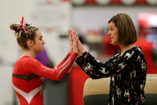 Manitowoc Lincoln's Tatum Bartow talks to coach Jacque Bartow after a vault during a December 2018 invitational. Gymnastics co-ops have won all but four D1 state titles this century.