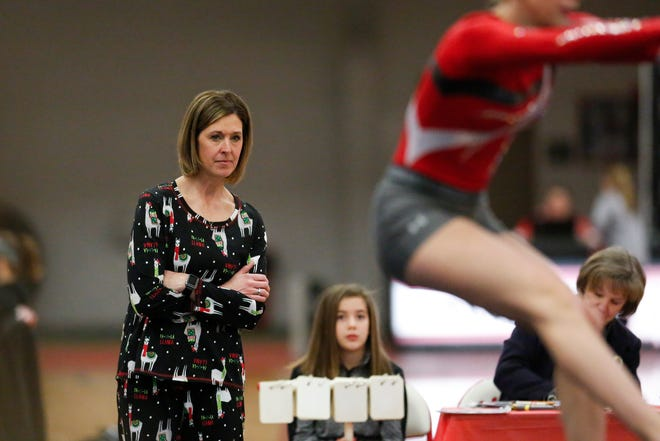 Manitowoc Lincoln coach Jacque Bartow watches her team warm up before the floor exercise during the Manitowoc Holiday Gymnastics Invitational last month.