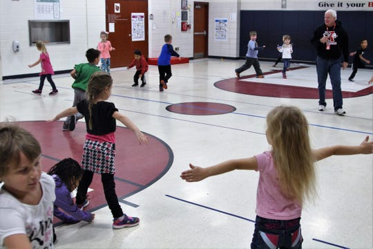 Tony Webber, who teaches physical education at Benjamin Harrison Elementary School, oversees a group of kindergartners as they run across the gym. The school has seen an influx of kindergartners this school year. As of December, there were 28 students in each of the three kindergarten classes.
