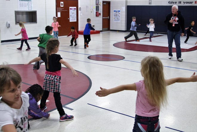 Tony Webber, who teaches physical education at Benjamin Harrison Elementary School, oversees a group of kindergartners as they run across the gym Friday afternoon. The school has seen an influx of kindergartners this year with 28 students in each of the three classes.