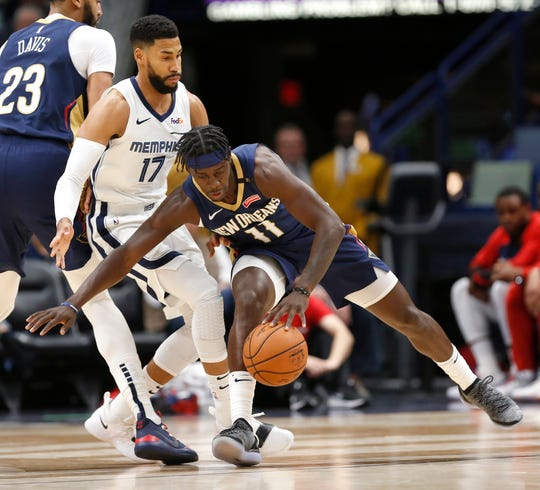 New Orleans Pelicans guard Jrue Holiday (11) is guarded by Memphis Grizzlies guard Garrett Temple (17) on Friday in New Orleans.