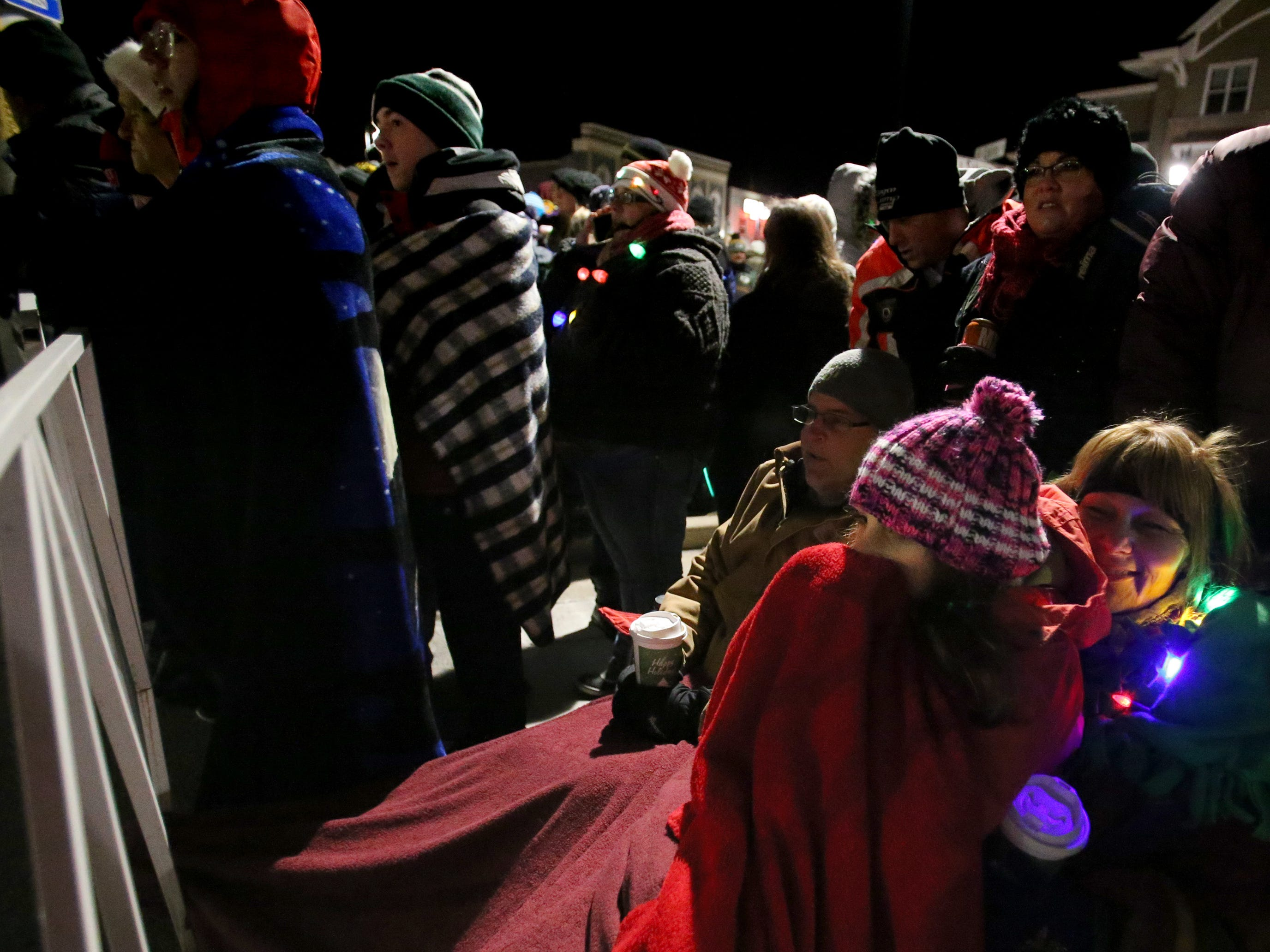 Gracie Gregory keeps warm with her mother Holly and Dad Joel against the barrier while waiting for the Canadian Pacific Holiday Train in Oconomowoc on Dec. 7.