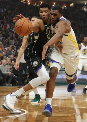 Bucks forward Giannis Antetokounmpo (34) and Warriors forward Kevon Looney  compete for a loose ball during the first half Friday night.