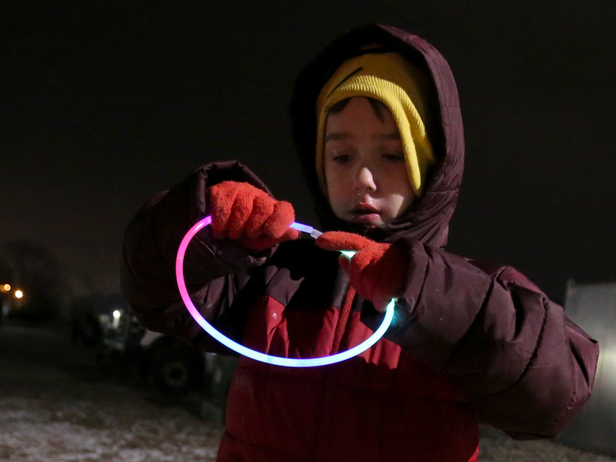 Vaughn Bertelson, 6, connects a glow-in-the-dark necklace while waiting for the Canadian Pacific Holiday Train in Oconomowoc on Dec. 7.