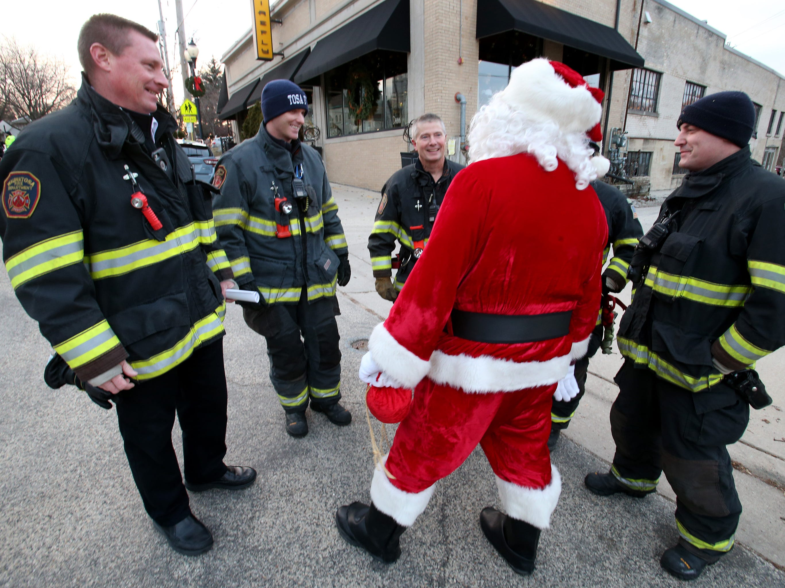 Santa stops to talk with a group of Wauwatosa Fire Department firefighters on duty at the Canadian Pacific Holiday Train stop in downtown Wauwatosa on Dec. 7.