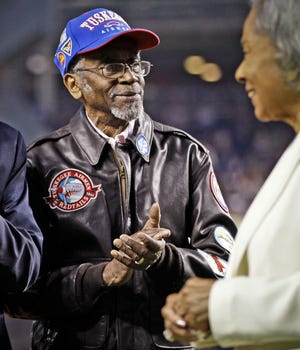 FILE - This photo from Sunday, April 15, 2012, shows Tuskeegee Airman Wilfred DeFour, left, with Jackie Robinson's widow Rachel Robinson, right, on Jackie Robinson Day at a New York Yankees' baseball game in New York. Police say a health aide found DeFour, 100, unconscious and unresponsive inside his Harlem apartment Saturday