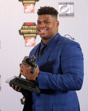 Alabama's Quinnen Williams poses with the trophy after winning the Outland Trophy as the nation's best interior lineman in college football, Thursday, Dec. 6, 2018, in Atlanta. (AP Photo/John Bazemore)