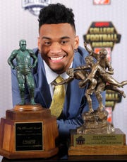 Alabama quarterback Tua Tagovailoa poses with the trophies after winning the Maxwell Award, left, for outstanding collegiate football player, and the Walter Camp award for player of the year, Thursday, Dec. 6, 2018, in Atlanta. (AP Photo/John Bazemore)