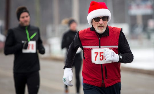 Runners take to the streets in the cold for the Yorktown Volunteer Firefighter's Association third annual Fire and Ice Holiday 5K run and walk in 2018 in downtown Yorktown.
