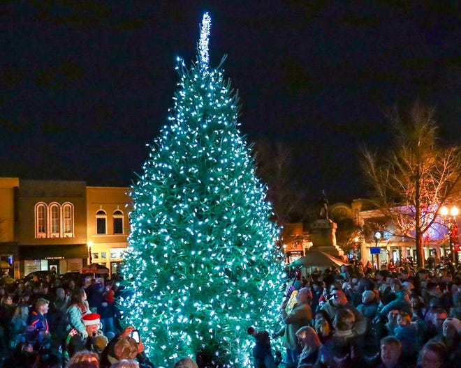 People gather next to the live tree during the Main Street Murfreesboro's annual Christmas tree lighting on Friday, December 7, 2018, in Murfreesboro, Tenn.
