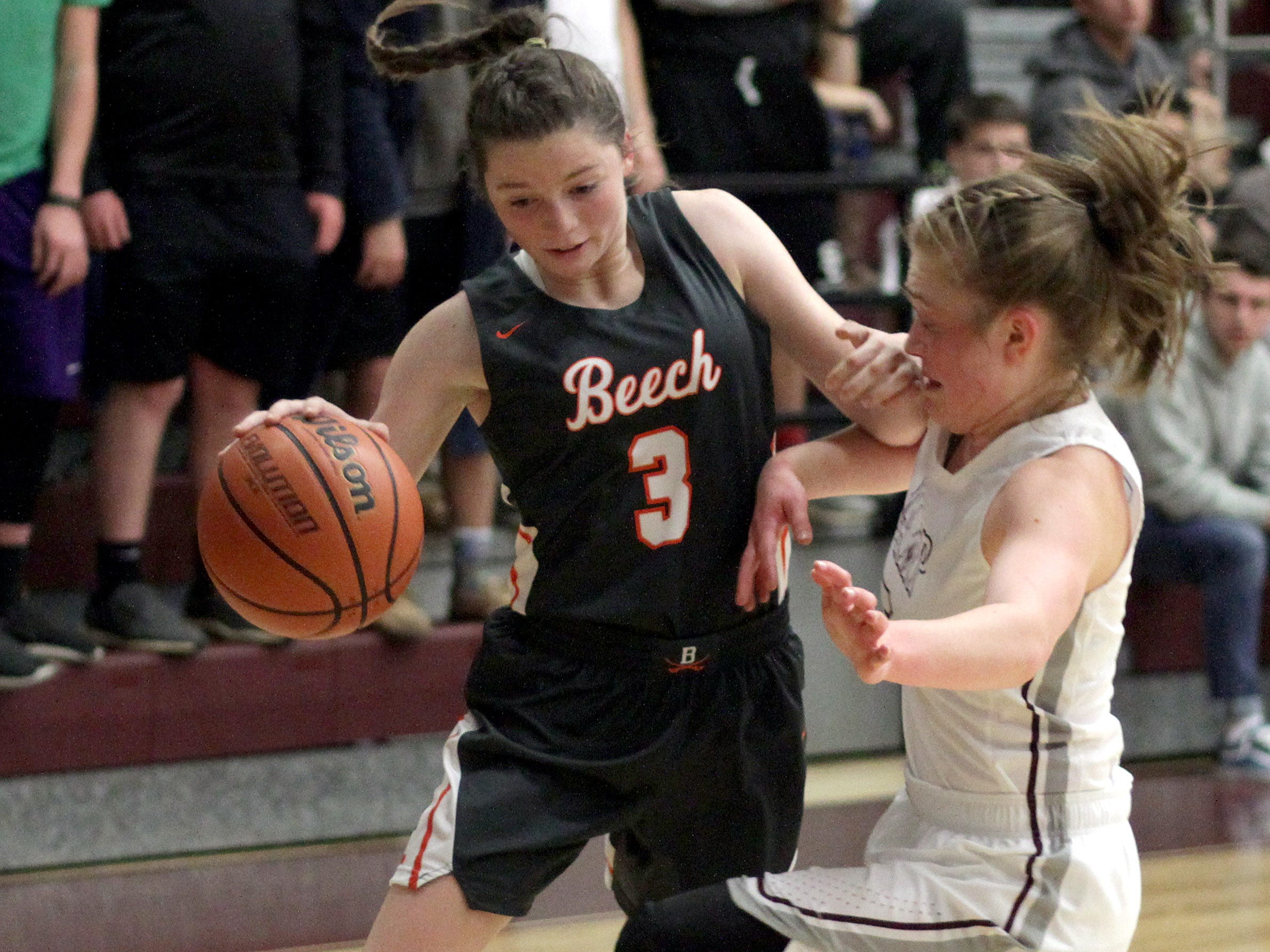 L-R Beech's Jana Claire Swafford drives into Station Camp's Keely Gatterland on Friday, December 7, 2018.