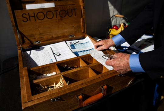 Brendan Cunningham, the tee announcer, arranges the scorecards before the players arrive at the first tee during the 30th annual QBE Shootout second round on Saturday at Tiburón Golf Club in Naples.