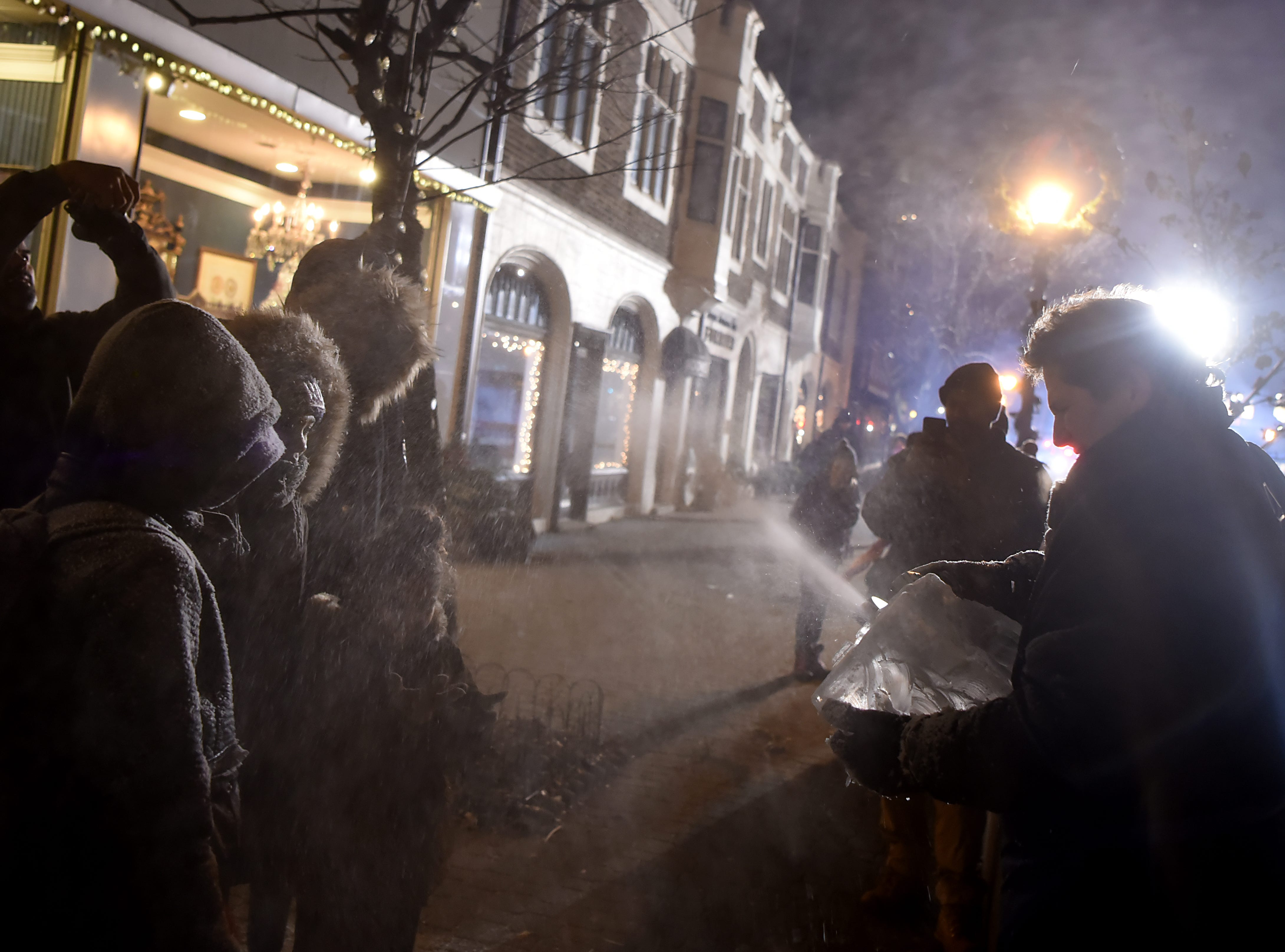 Jimmy Chiappa of Jimmy's Artistic Creations, sprays children with snow as he carves a chunk of ice during the Montclair tree lighting in Montclair  on Friday December 7, 2018.