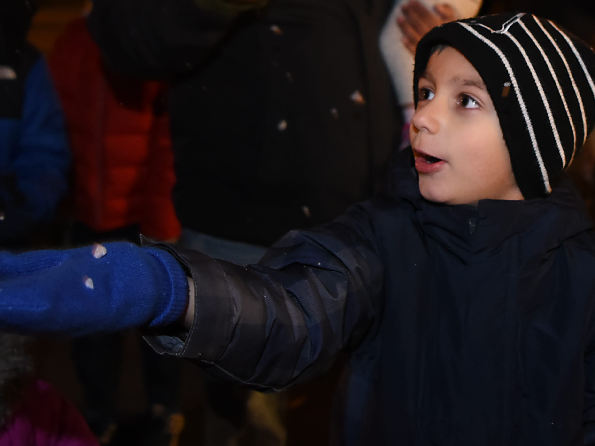 Rafel Calderon, 5, catches some snow from the snow machine on his mitten during the Montclair tree lighting in Montclair  on Friday December 7, 2018.