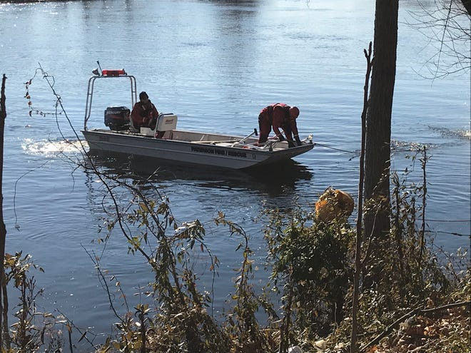 Paterson fire and rescue members try to help the county scuba team members remove a car from the river.