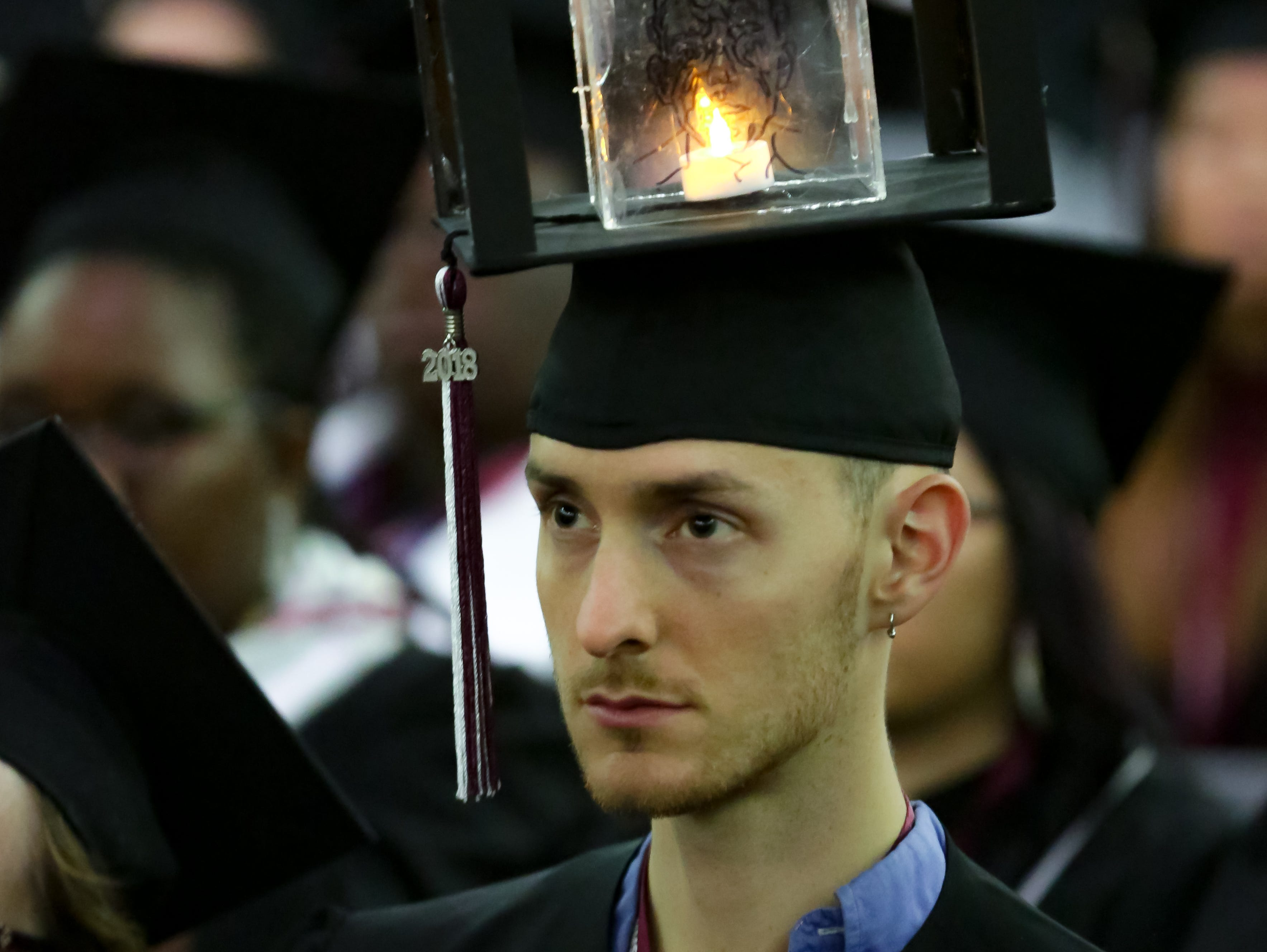 Henry Hartig wears a mortar board he designed himself during NMSU commencement on Saturday, Dec. 8, 2018 at the Pan American Center. Hartig said the art was a self portrait.