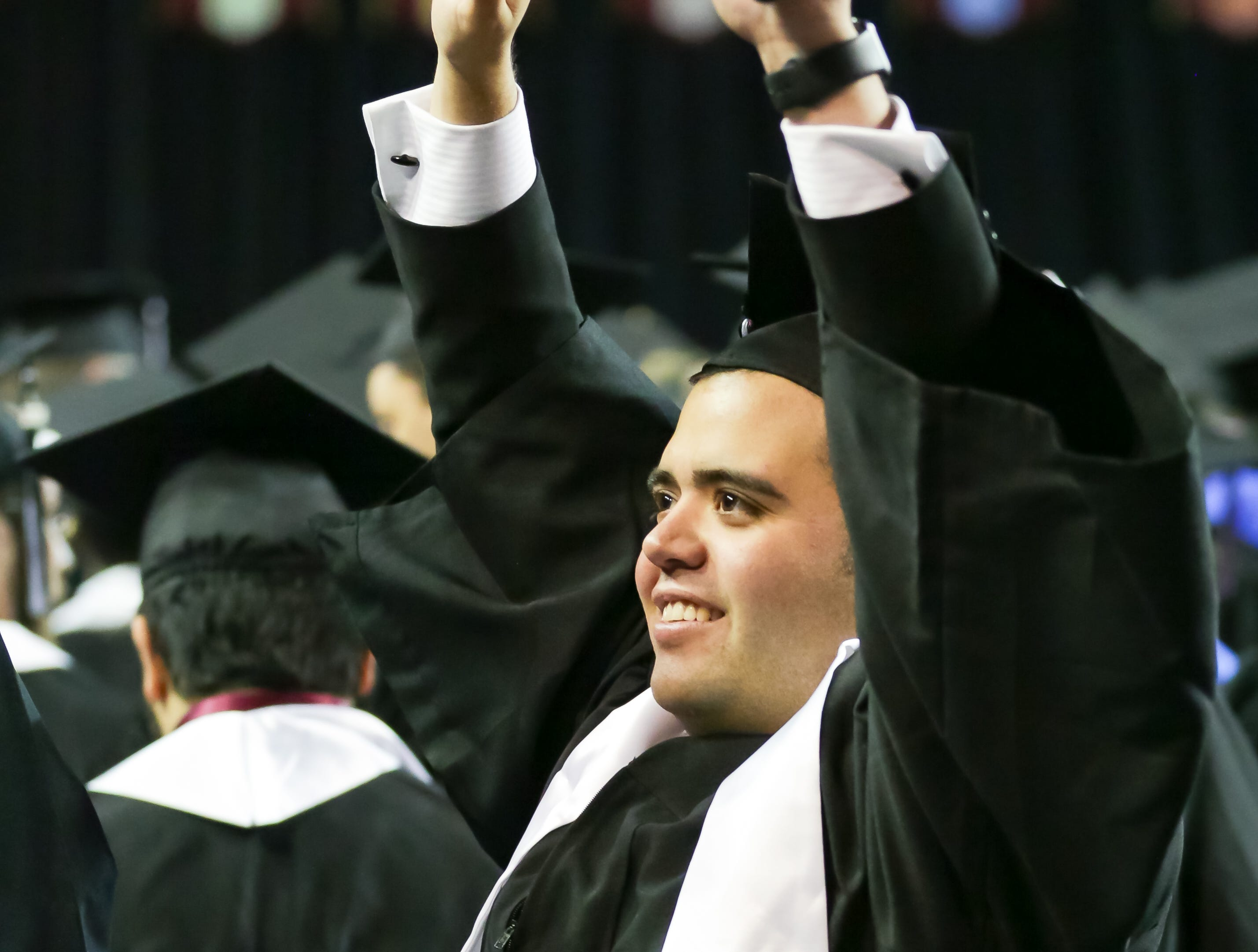 New Mexico State University's Eugenio Campos Leal waves at loved ones during the start of NMSU commencement ceremony on Saturday, Dec. 8, 2018 at the Pan American Center.