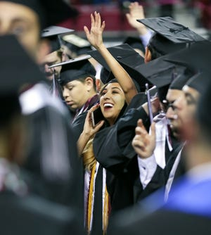 New Mexico State University graduate Nichole Gomez waves at loved ones during the start of the NMSU commencement ceremony on Saturday, Dec. 8, 2018 at the Pan American Center.