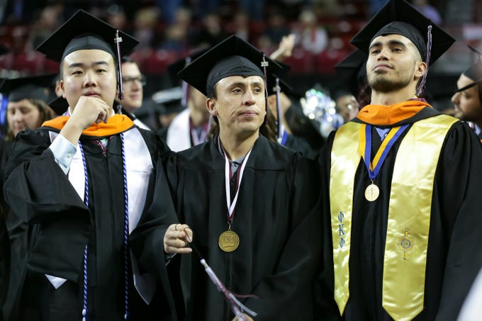 NMSU's Amo Cheng, left, Eduardo Davila, center, and Daniel Diaz look on during the start of NMSU commencement ceremony on Saturday, Dec. 8, 2018 at the Pan American Center.