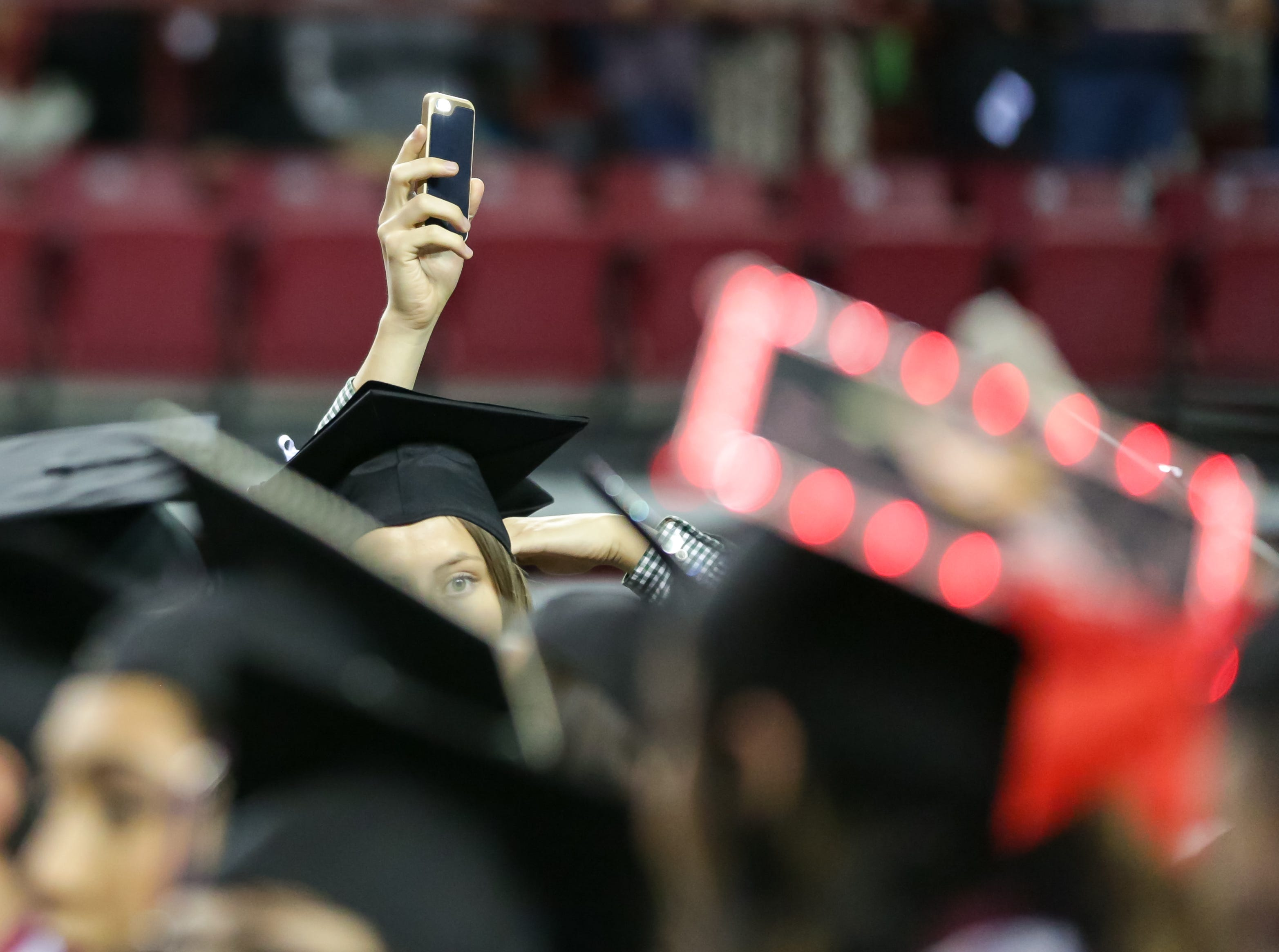 New Mexico State University students  wave to loved ones with the flashlights of their phones during the start of NMSU commencement ceremony on Saturday, Dec. 8, 2018 at the Pan American Center.