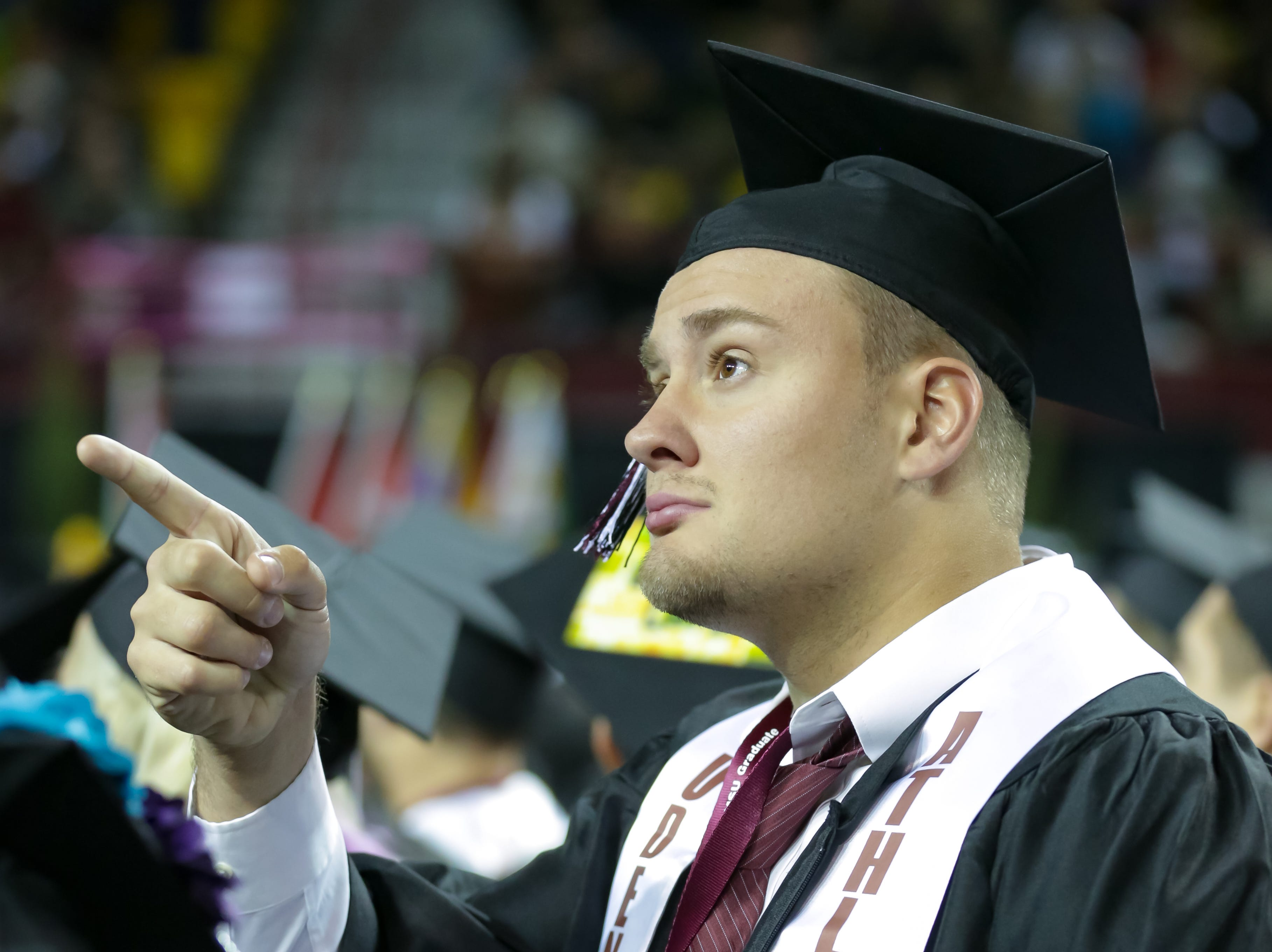 New Mexico State University's Jackson Solbeck points up at loved ones during the start of NMSU commencement ceremony on Saturday, Dec. 8, 2018 at the Pan American Center.