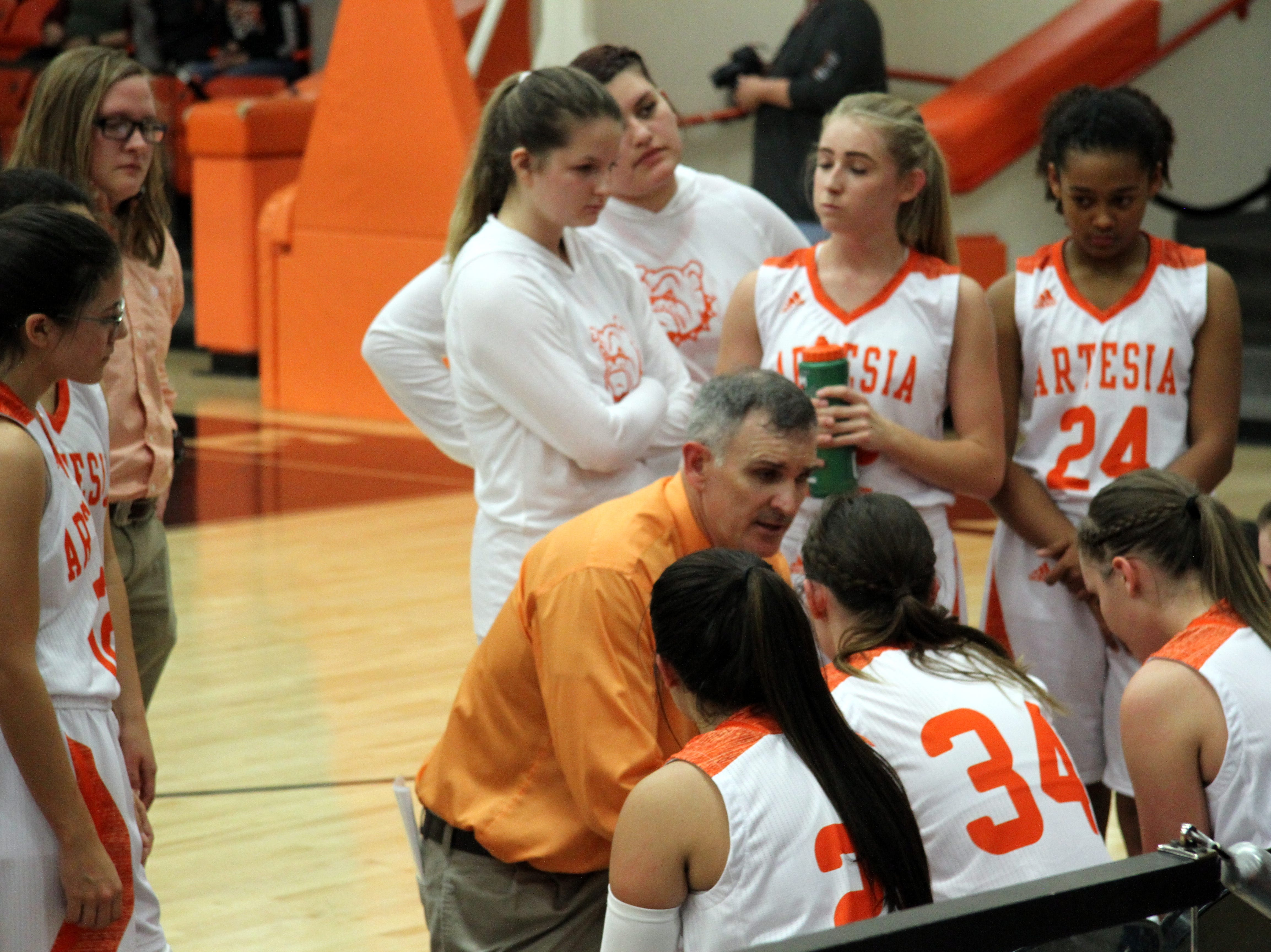 Artesia girls coach Jeff Houghtaling talks to his team during a timeout against Deming.