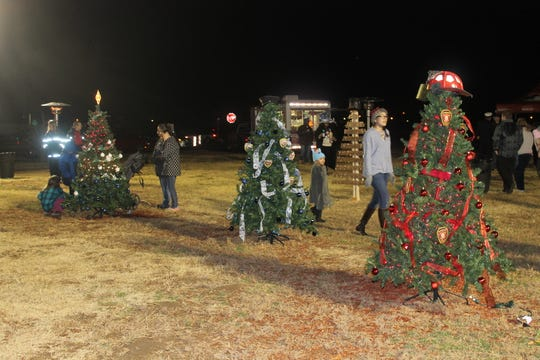 The Alamogordo Fire and Police departments decorated trees for the tree-lighting event, and there was an unlit tree to commemorate fallen service members.
