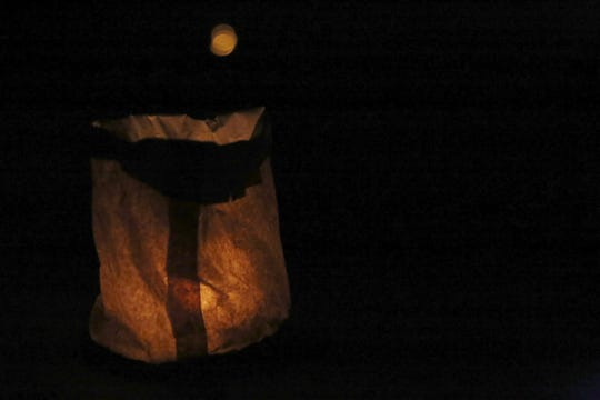 A luminaria glows Friday in Riverside Park in Aztec during River Glo.
