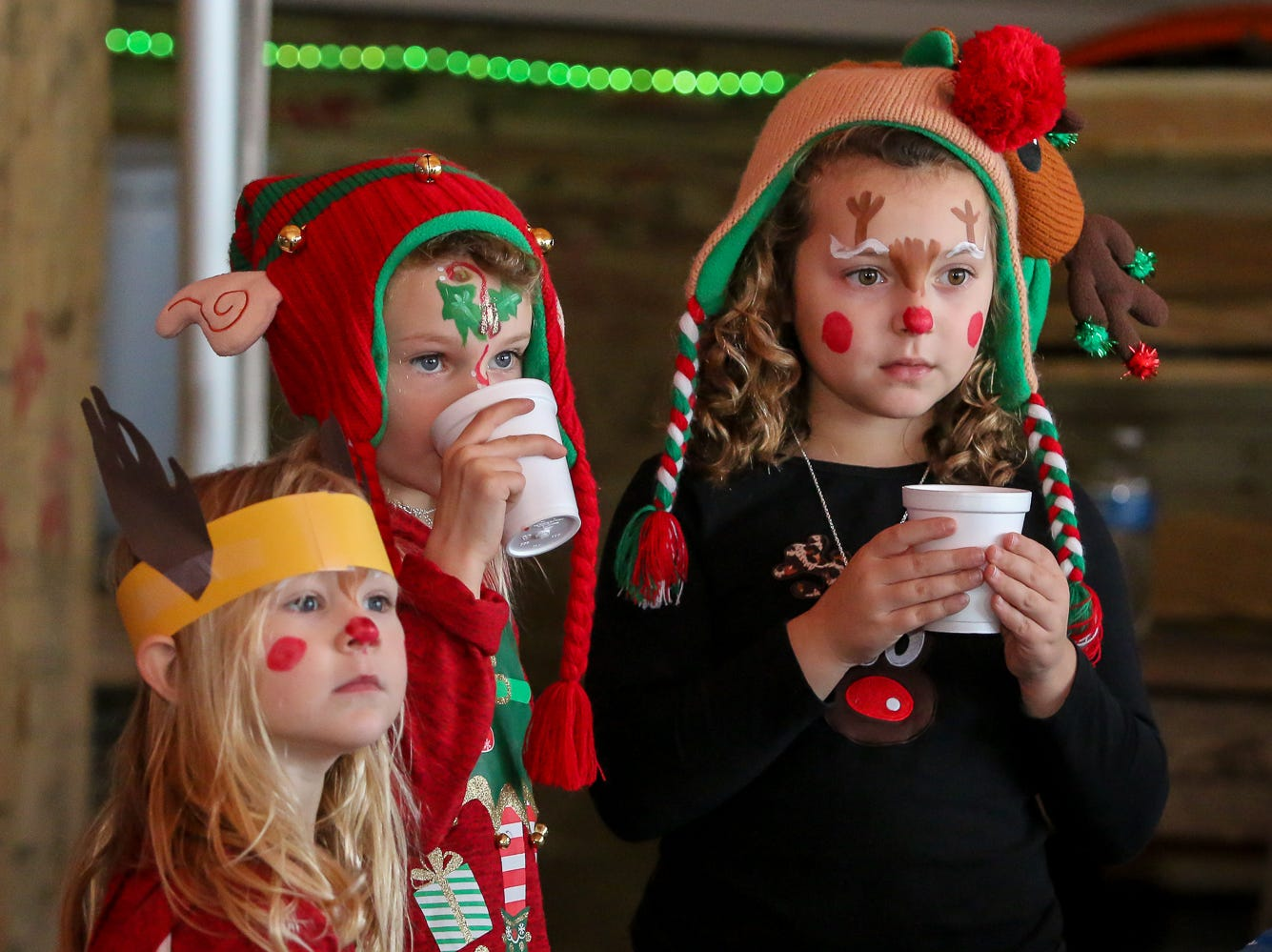 Kids enjoy warm drinks and watch as others have their face painted during the Santa Drop at the Flora-Bama Lounge, Package and Oyster Bar on Saturday, December 8, 2018. Usually Santa arrives by parachuting in, however, was unable to do to due to the weather.