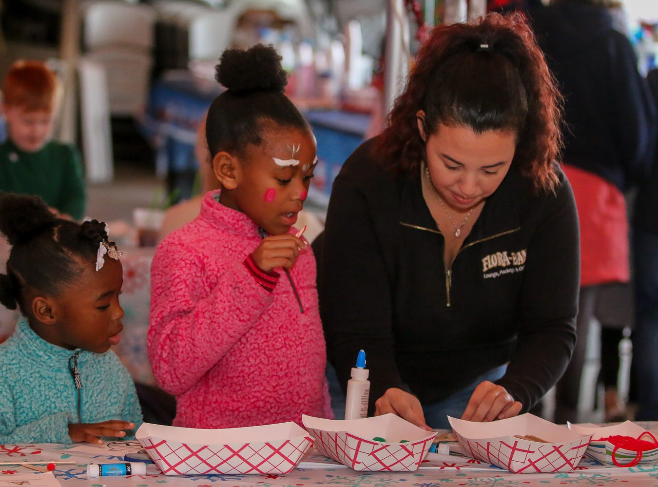Zhea Bonner, 5, left, and Harmony Johnson, 7, watch as Beverly Gravitt shows them how to do a craft during the Santa Drop at the Flora-Bama Lounge, Package and Oyster Bar on Saturday, December 8, 2018. Usually Santa arrives by parachuting in, however, was unable to do to due to the weather.