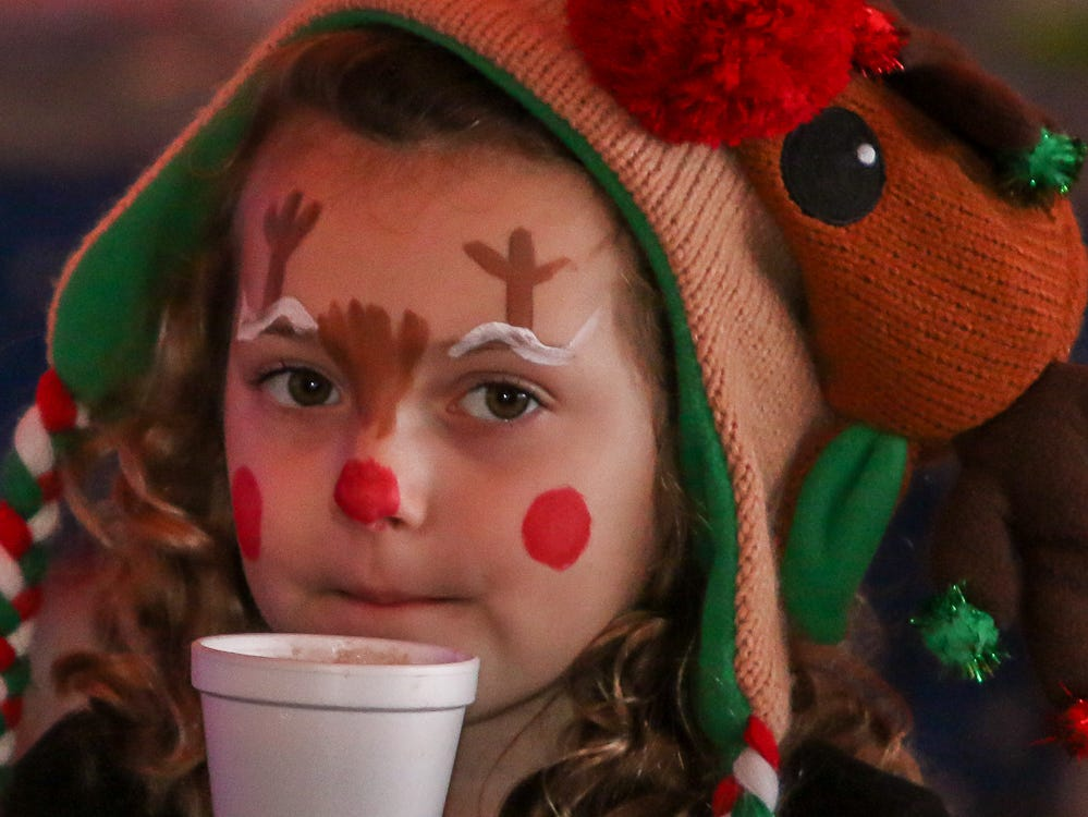 Ava Weber, 7, blows on her hot chocolate before drinking some of it during the Santa Drop at the Flora-Bama Lounge, Package and Oyster Bar on Saturday, December 8, 2018. Usually Santa arrives by parachuting in, however, was unable to do to due to the weather.