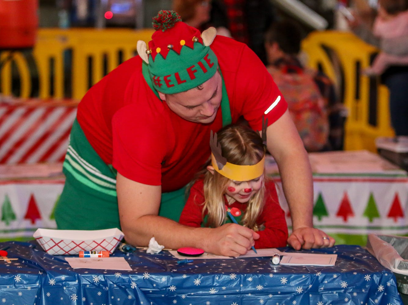 Jake Cavanaugh and his daughter, Jordyn, 3, work together to complete an activity during the Santa Drop at the Flora-Bama Lounge, Package and Oyster Bar on Saturday, December 8, 2018. Usually Santa arrives by parachuting in, however, was unable to do to due to the weather.