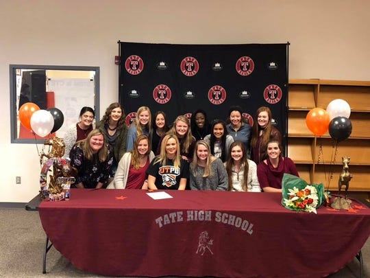 Tate High senior Grace Talbert (center, black shirt) celebrates with teammates after signing with the University of Texas-Permian  Basin.