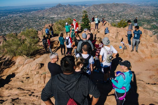 """Hikers wait in line to take a photo with John Cressey, the """"Camelback Santa"""" at the top of Camelback Mountain in Phoenix, Arizona on Dec. 8, 2018."""