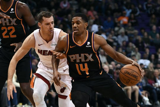 Suns guard De'Anthony Melton handles the ball while being defended by Heat guard Goran Dragic during the second half of a game Dec. 7 at Talking Stick Resort Arena.