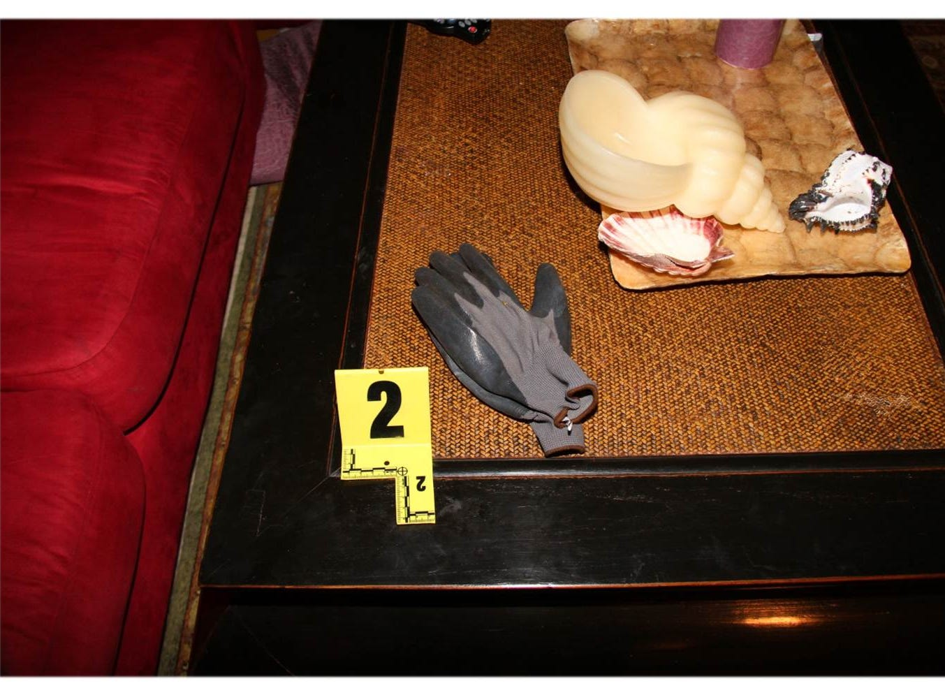 An evidence marker points to a pair of gloves sitting on a piece of furniture.