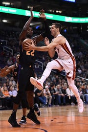 Dec 7, 2018; Phoenix, AZ, USA; Miami Heat guard Goran Dragic (7) makes a pass in front of Phoenix Suns center Deandre Ayton (22) in the first half at Talking Stick Resort Arena. Mandatory Credit: Jennifer Stewart-USA TODAY Sports