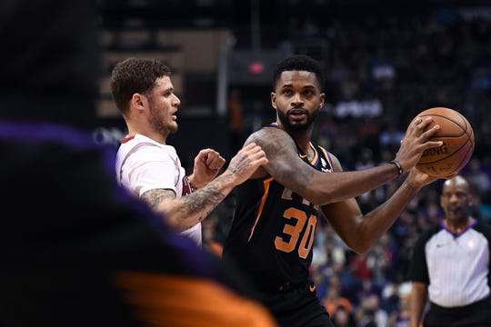 Suns guard Troy Daniels looks to move the ball while being defended by Heat guard Tyler Johnson.