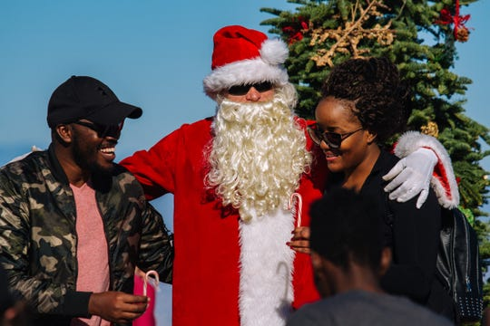 """Hikers take a photo with John Cressey, the """"Camelback Santa"""" at the top of Camelback Mountain in Phoenix, Arizona on Dec. 8, 2018."""