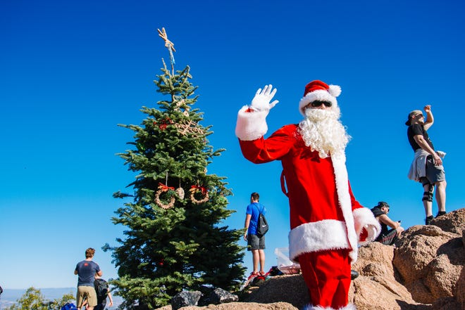 """John Cressey, the """"Camelback Santa"""" poses with hikers at the top of Camelback Mountain in Phoenix, Arizona on Dec. 8, 2018."""