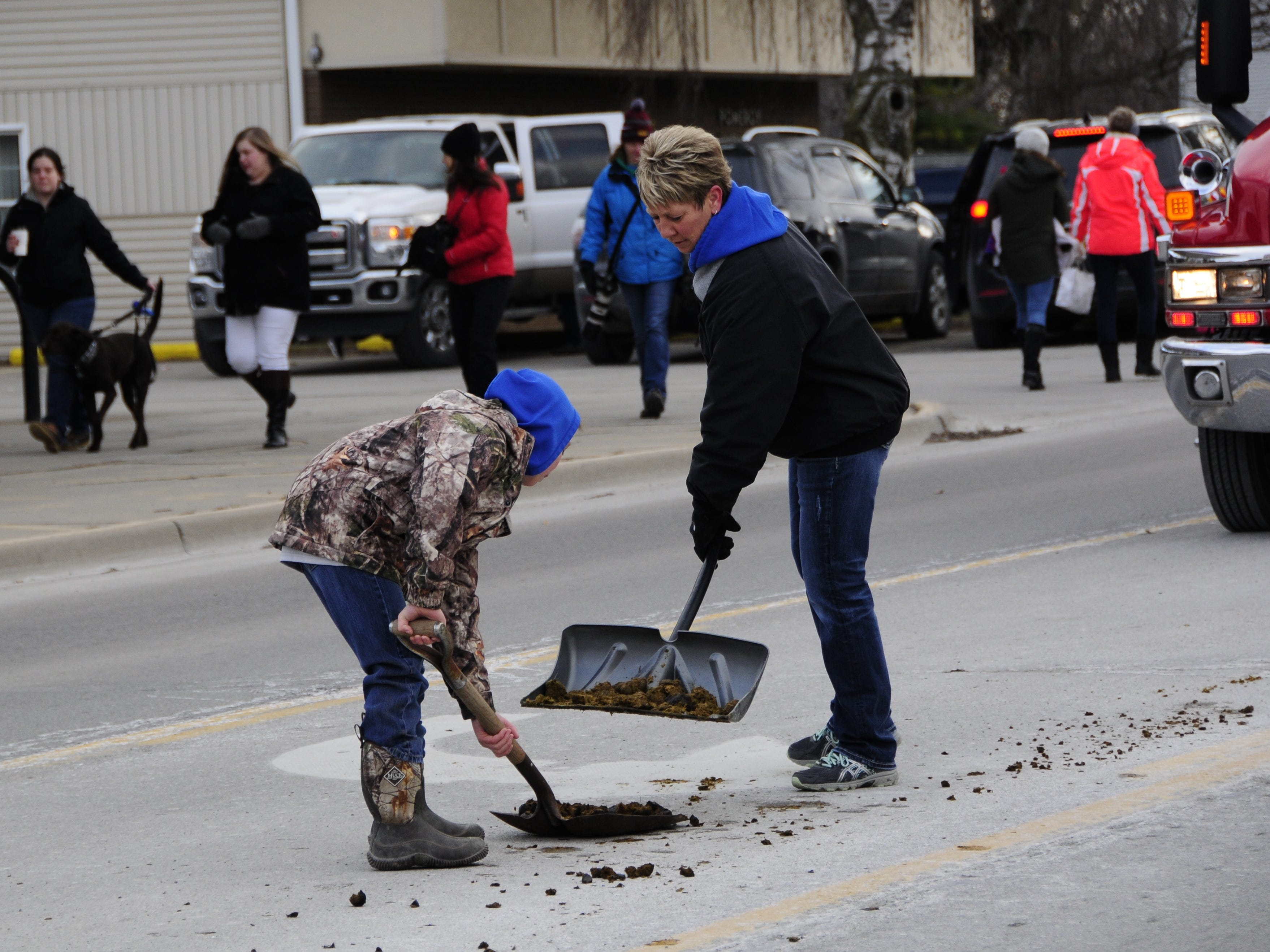 Lorie and Branden Soule clean up after the Lexington Old-Fashioned Christmas Horse Parade on Saturday, Dec. 8, 2018.