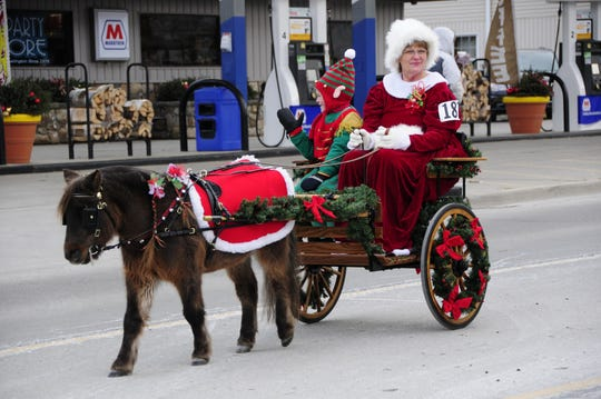 Mrs. Claus, Bonnie Youngblood, and an elf helper ride in a cart drawn by miniature horse Zoar.