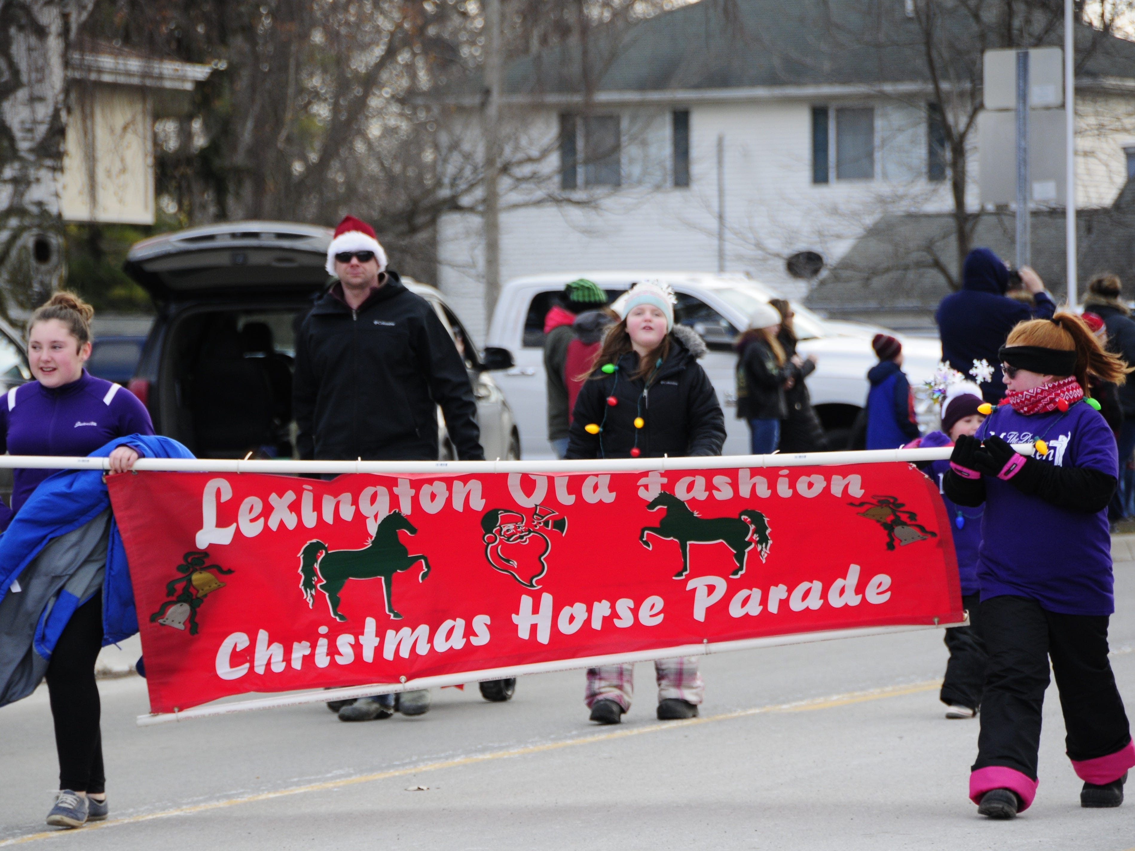 Kids march with a banner at the start of the Lexington Old-Fashioned Christmas Horse Parade on Saturday, Dec. 8, 2018.